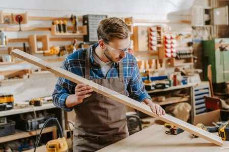 Photo for Handsome carpenter in goggles holding wooden plank - Royalty Free Image