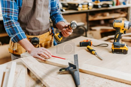 Photo for Cropped view of carpenter holding hammer drill - Royalty Free Image