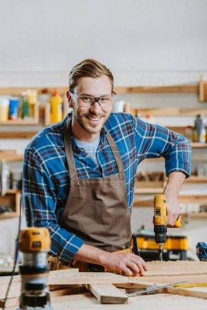 Photo pour Foyer sélectif de charpentier joyeux dans les lunettes et tablier tenant marteau perceuse près des planches de bois - image libre de droit