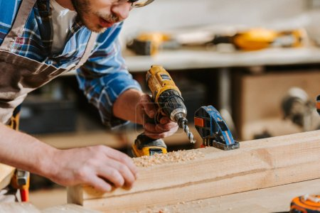 Photo for Cropped view of bearded carpenter in apron holding hammer drill near wooden planks - Royalty Free Image