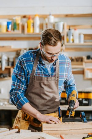 Photo for Selective focus of carpenter in safety glasses and apron holding hammer drill near wooden planks - Royalty Free Image