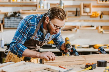 Photo for Selective focus of carpenter in safety glasses and apron holding hammer drill and blowing on sawdust near wooden plank - Royalty Free Image