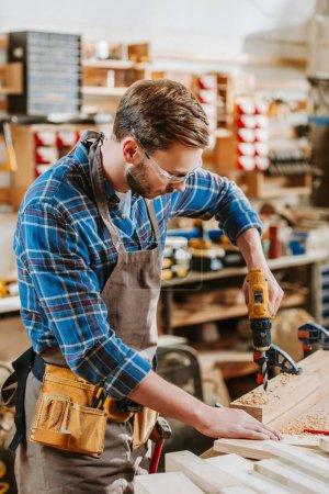 Photo pour Foyer sélectif du menuisier dans les lunettes et tablier tenant marteau perceuse près des planches de bois - image libre de droit