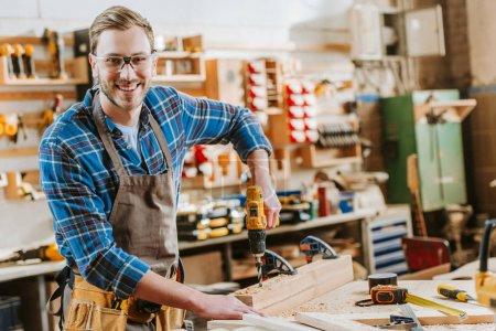 Photo pour Travailleur du bois heureux dans les lunettes et tablier tenant marteau perceuse près des planches de bois - image libre de droit