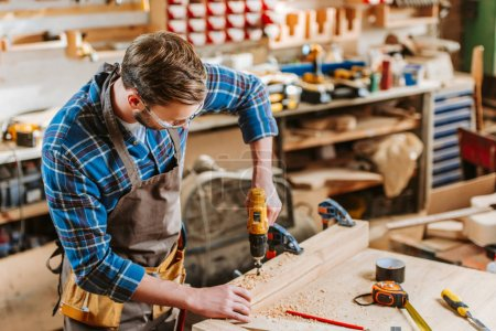 Photo for Woodworker in goggles and apron holding hammer drill near wooden planks - Royalty Free Image