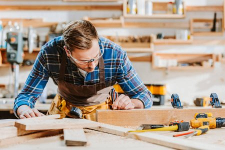 selective focus of woodworker in goggles touching wooden dowel