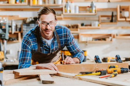 Photo for Selective focus of happy carpenter in goggles touching wooden dowel - Royalty Free Image