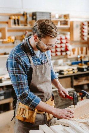 Photo pour Menuisier dans des lunettes tenant marteau près de cheville en bois - image libre de droit
