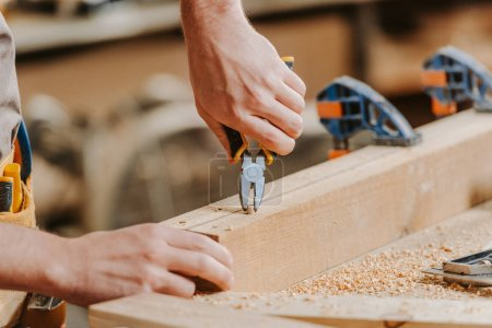 Photo for Cropped view of carpenter holding pliers near wooden dowel - Royalty Free Image