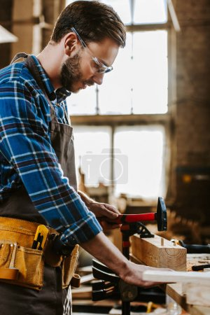 Photo for Side view of carpenter holding hammer in workshop - Royalty Free Image