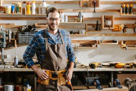 Photo pour Charpentier joyeux dans des lunettes debout et touchant ceinture d'outils dans l'atelier - image libre de droit