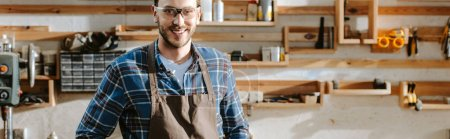Photo for Panoramic shot of cheerful carpenter in apron looking at camera in workshop - Royalty Free Image