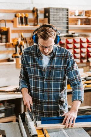 Photo for Handsome carpenter in protective headphones holding plank near circular saw - Royalty Free Image