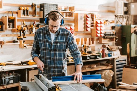 Photo for Handsome woodworker in protective headphones holding plank near circular saw - Royalty Free Image
