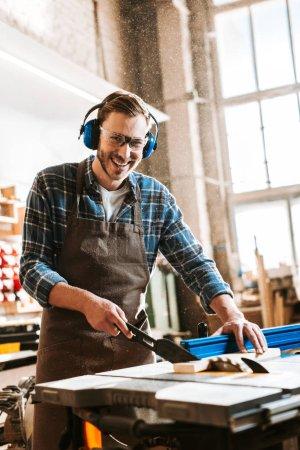 Photo pour Travailleur du bois joyeux dans les écouteurs de protection et tablier tenant la planche près de la scie circulaire - image libre de droit