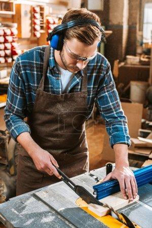 Photo pour Travailleur du bois barbu dans les écouteurs de protection et tablier tenant la planche près de la scie circulaire - image libre de droit