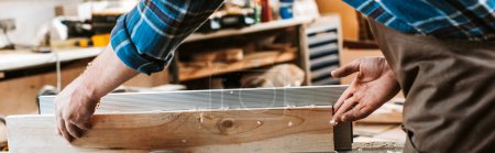 Photo for Panoramic shot of woodworker holding plank near circular saw in carpentry shop - Royalty Free Image