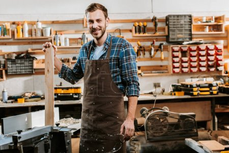 Photo for Cheerful carpenter in apron standing and holding wooden plank in workshop - Royalty Free Image