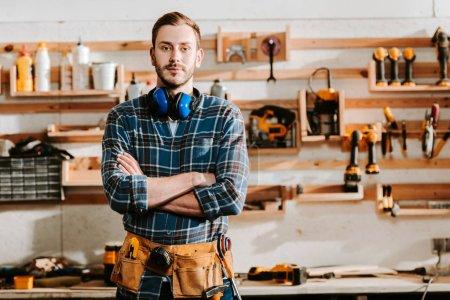 Photo pour Beau menuisier en tablier debout avec bras croisés en atelier - image libre de droit