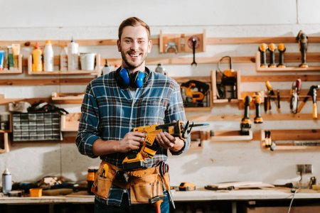 Photo for Happy bearded carpenter holding hammer drill in workshop - Royalty Free Image