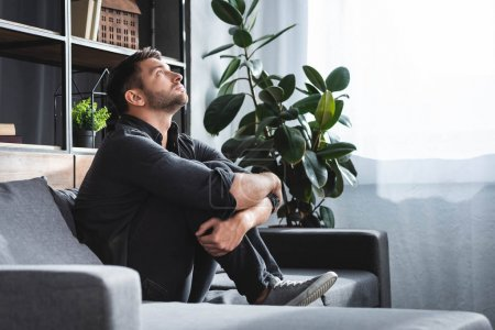 Photo for Side view of handsome man with panic attack sitting on sofa and hugging legs in apartment - Royalty Free Image