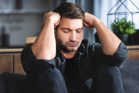 Photo pour Handsome man in black shirt with headache touching head in apartment - image libre de droit