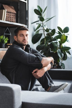 Photo for Handsome man with panic attack sitting on sofa and hugging legs in apartment - Royalty Free Image