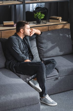 Photo for High angle view of handsome and pensive man sitting on sofa in apartment - Royalty Free Image