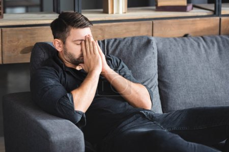 Photo for Man with headache sitting on sofa and obscuring face in apartment - Royalty Free Image