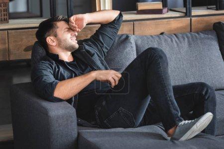 Photo pour Bel homme souffrant de maux de tête assis sur un canapé et touchant la tête dans l'appartement - image libre de droit