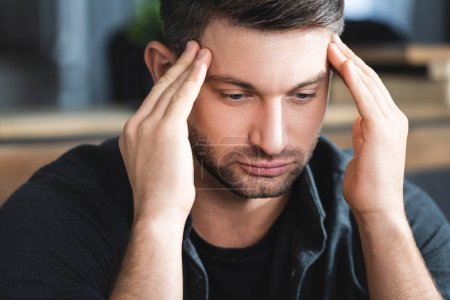 Photo pour Handsome man with headache touching head and looking down in apartment - image libre de droit