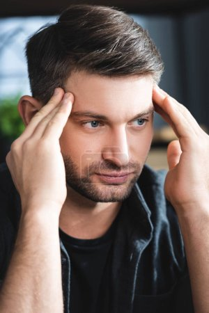 Photo for Handsome man with headache touching head and looking away in apartment - Royalty Free Image