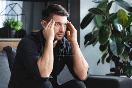 Photo for Handsome man in shirt with headache touching head in apartment - Royalty Free Image