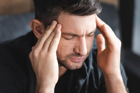 Photo for Handsome man with headache touching head in apartment - Royalty Free Image