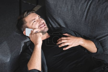 Photo for High angle view of handsome man having heart attack and talking on smartphone in apartment - Royalty Free Image