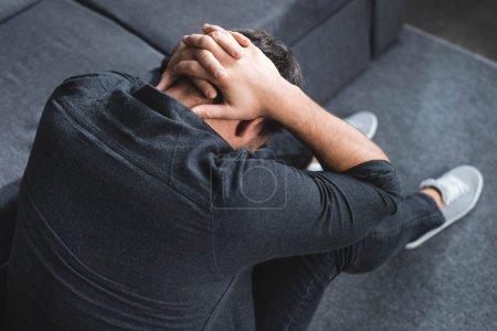 vista de ángulo alto del hombre con dolor de cabeza tocando la cabeza en el apartamento