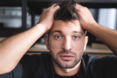 handsome man with panic attack touching head in apartment