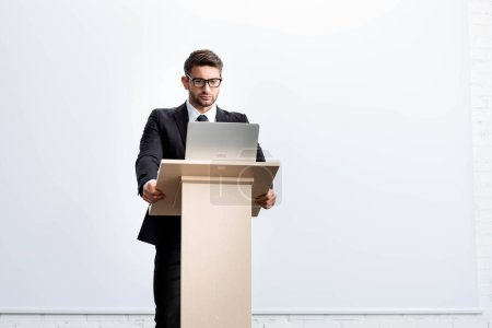 Photo for Businessman in suit standing at podium tribune and looking at laptop during conference isolated on white - Royalty Free Image
