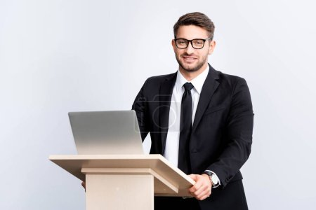 Photo for Smiling businessman in suit standing at podium tribune during conference isolated on white - Royalty Free Image