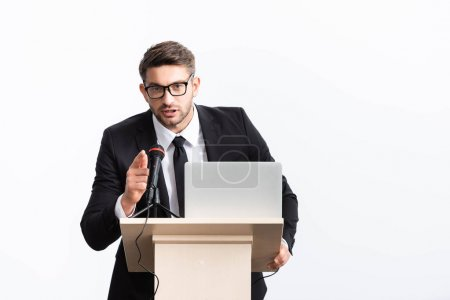 Photo for Businessman in suit standing at podium tribune and pointing with finger during conference isolated on white - Royalty Free Image