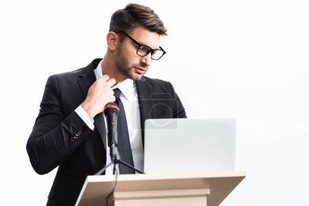 Photo for Stressed businessman in suit standing at podium tribune and looking at laptop during conference isolated on white - Royalty Free Image