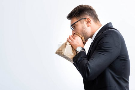 Photo for Side view of scared businessman in suit breathing in paper bag during conference isolated on white - Royalty Free Image