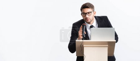 Photo pour Panoramic shot of businessman in suit standing at podium tribune and speaking during conference isolated on white - image libre de droit