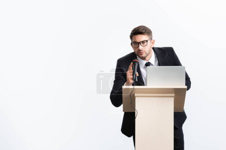 Photo pour Businessman in suit standing at podium tribune and speaking during conference isolated on white - image libre de droit