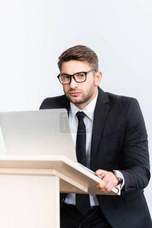 Photo pour Homme d'affaires effrayé en costume debout sur le podium tribune et regardant la caméra pendant la conférence isolé sur blanc - image libre de droit