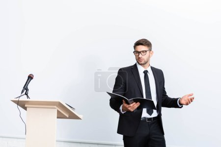 Photo for Businessman in suit holding folder and looking away during conference on white background - Royalty Free Image
