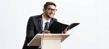 Photo for Panoramic shot of smiling businessman in suit standing at podium tribune and holding folder during conference isolated on white - Royalty Free Image