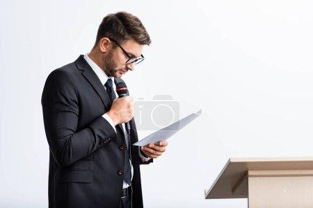 Photo pour Homme d'affaires en costume tenant le microphone et regardant le papier pendant la conférence isolé sur blanc - image libre de droit