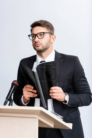 Photo for Businessman in suit standing at podium tribune and holding folder during conference isolated on white - Royalty Free Image