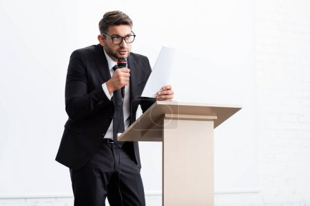Photo pour Scared businessman in suit standing at podium tribune and speaking during conference isolated on white - image libre de droit